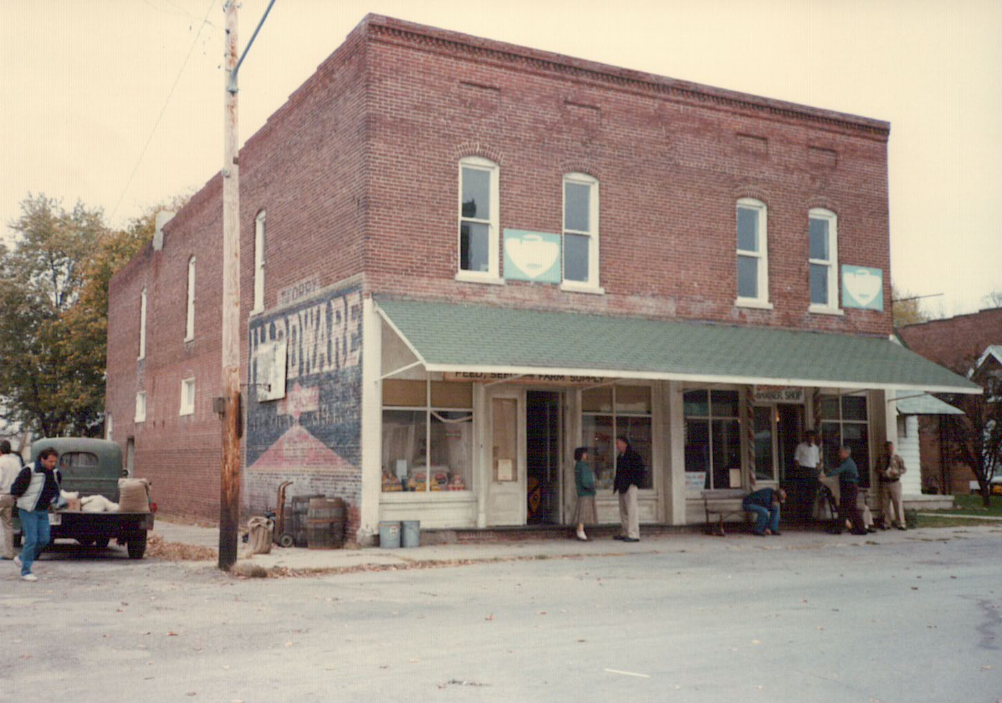 Director David Anspaugh (far left), Barbara Hershey and Hackman (center), and some townspeople in front of the feed-and-grain and barbershop, October 23, 1985