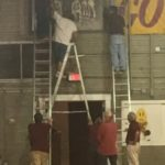 Hoosier Gym volunteers fasten the team photo to the wall.