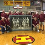 Hoosier Gym volunteers pose with the original team photo before it is placed on the wall.